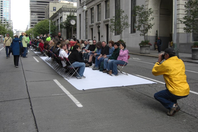 In Summer 2007, several hundred Seattle residents got downtown at 6am on a Sunday morning to participate in a city-sponsored photo shoot to demonstrate how much space different modes of public transport cost (e.g. bikes, cars, light rail and buses).  This was coordinated by I-Sustain.